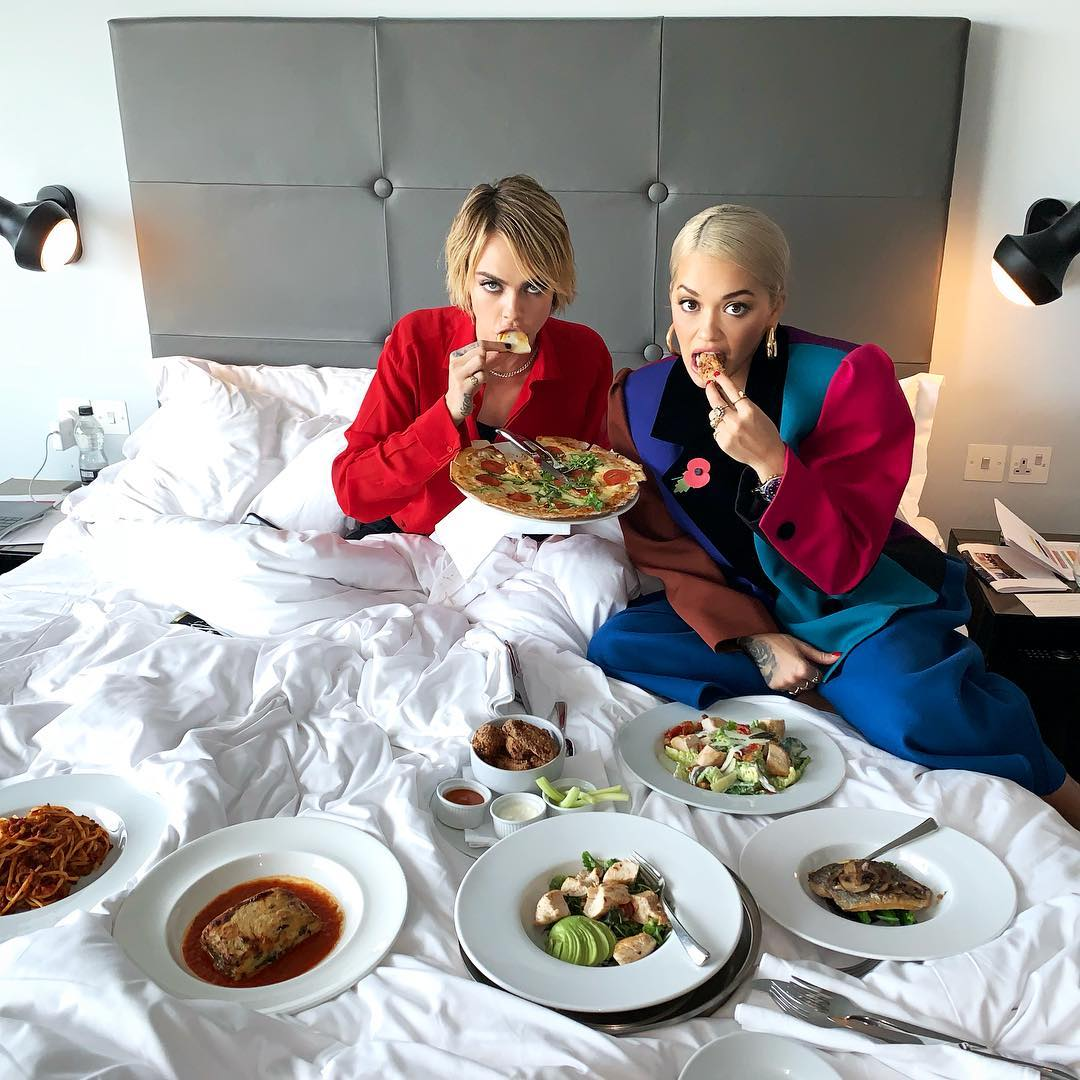 Rita Ora In Powersuit Is Eating With Cara Delevingne On A Bed 2019