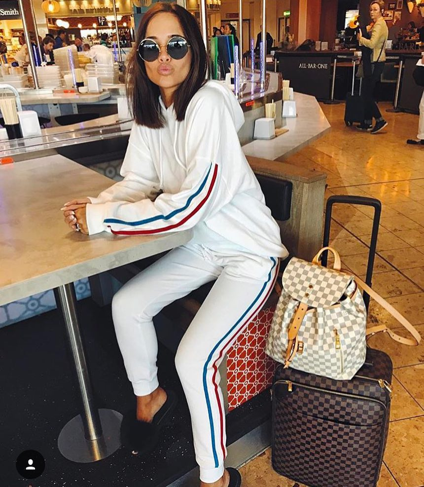 Airport Outfit Idea: White Tracksuit With Hoodie, Black Fluffy Slides And Rounded Sunglasses 2020