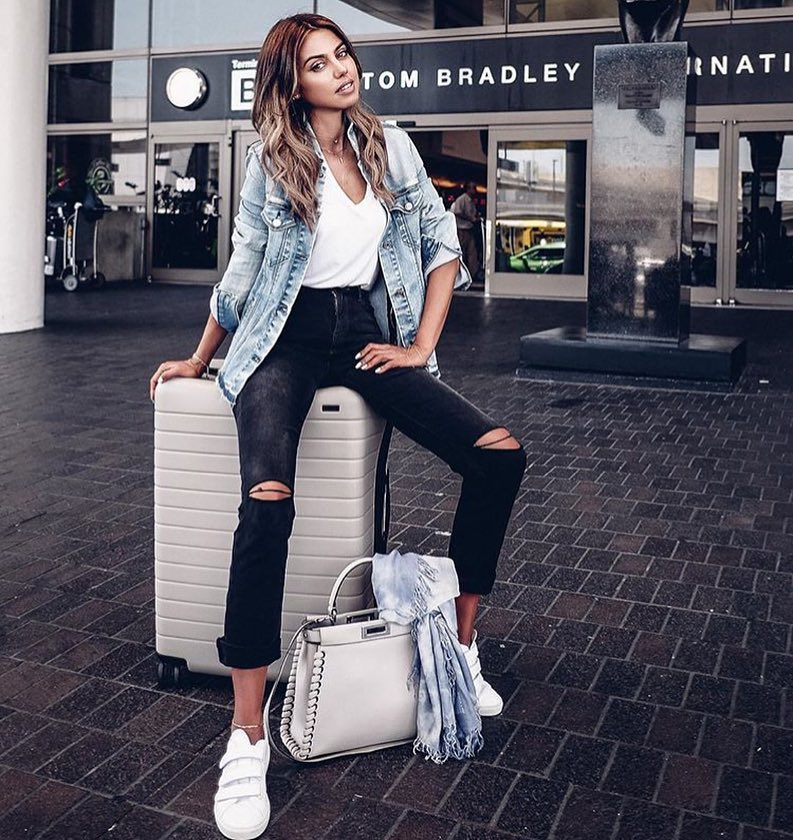 Casual Airport Outfit Idea: Blue Denim Jacket, Black Skinnies, White V-Neck And White Kicks 2019